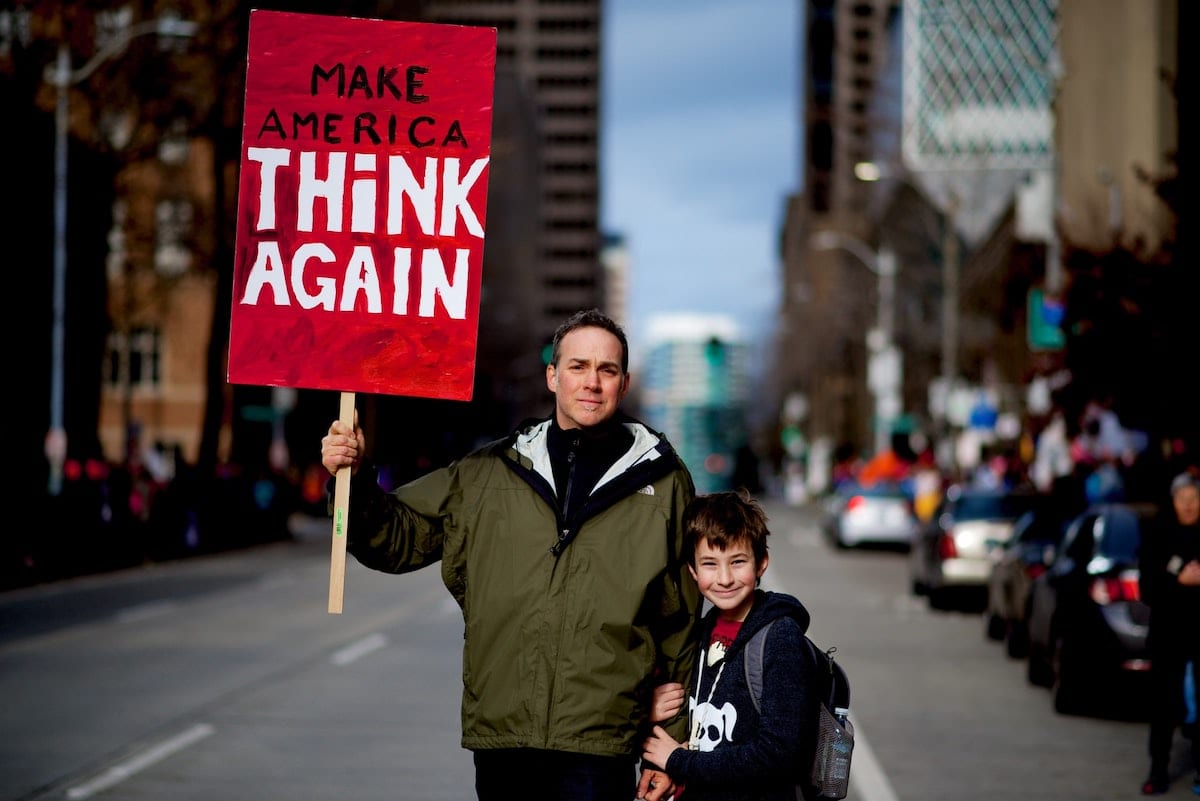 A proud father and son hold a sign calling for America to think again. An appropriate response for, among other things, Trump's tragic legacy of environmental deregulation.