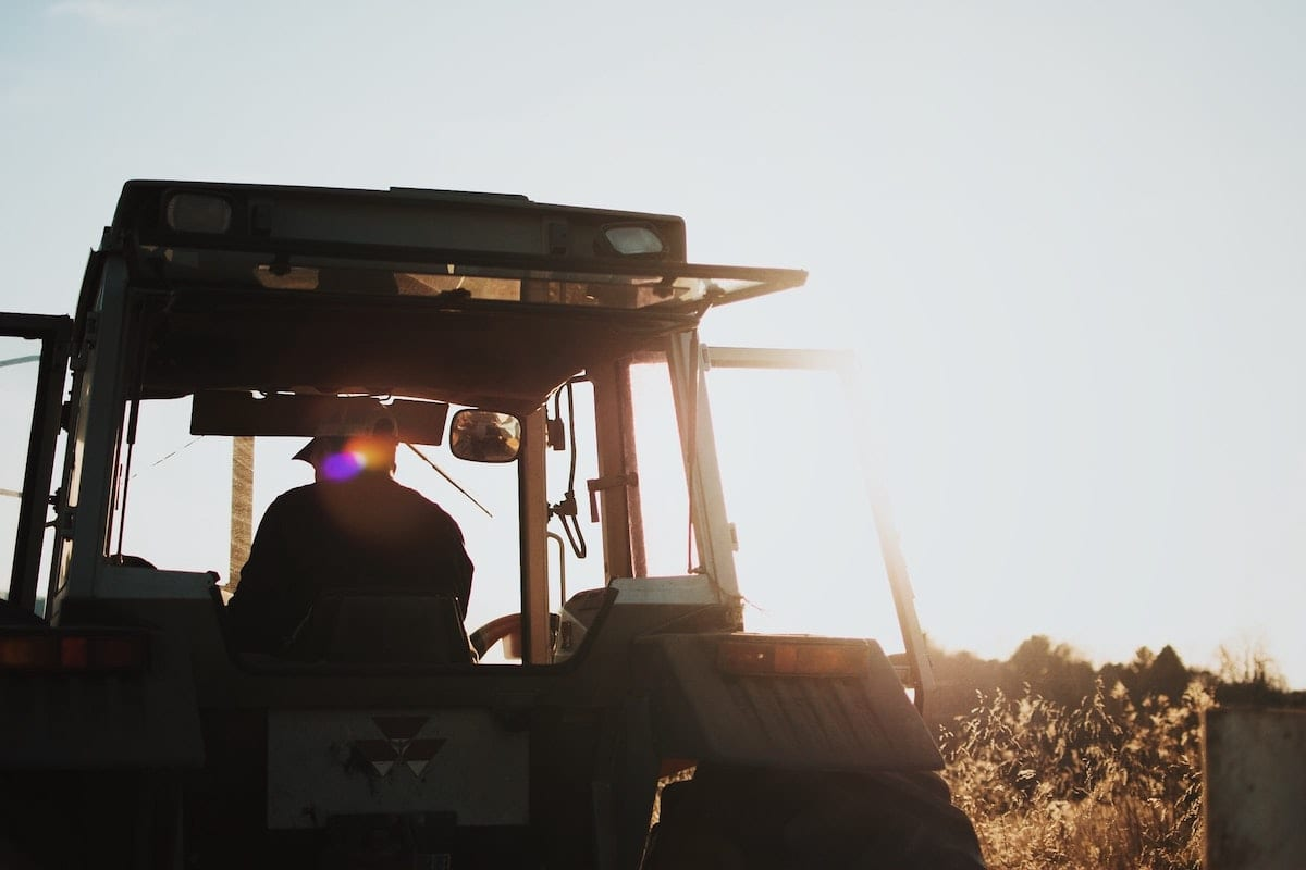 A fermer plows his fields in the morning sun