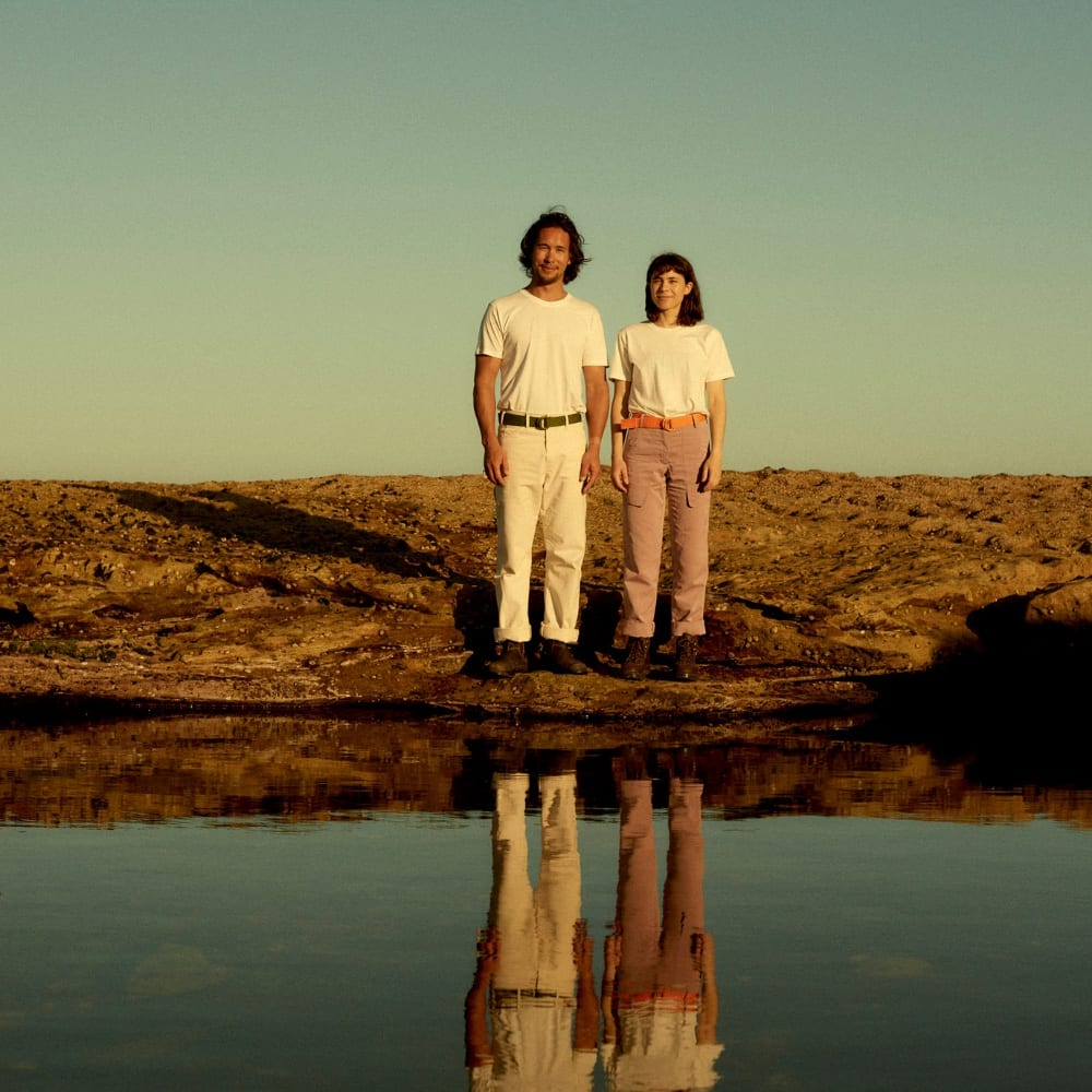 A man and woman stand near a shoreline wearing belts made from plastic waste