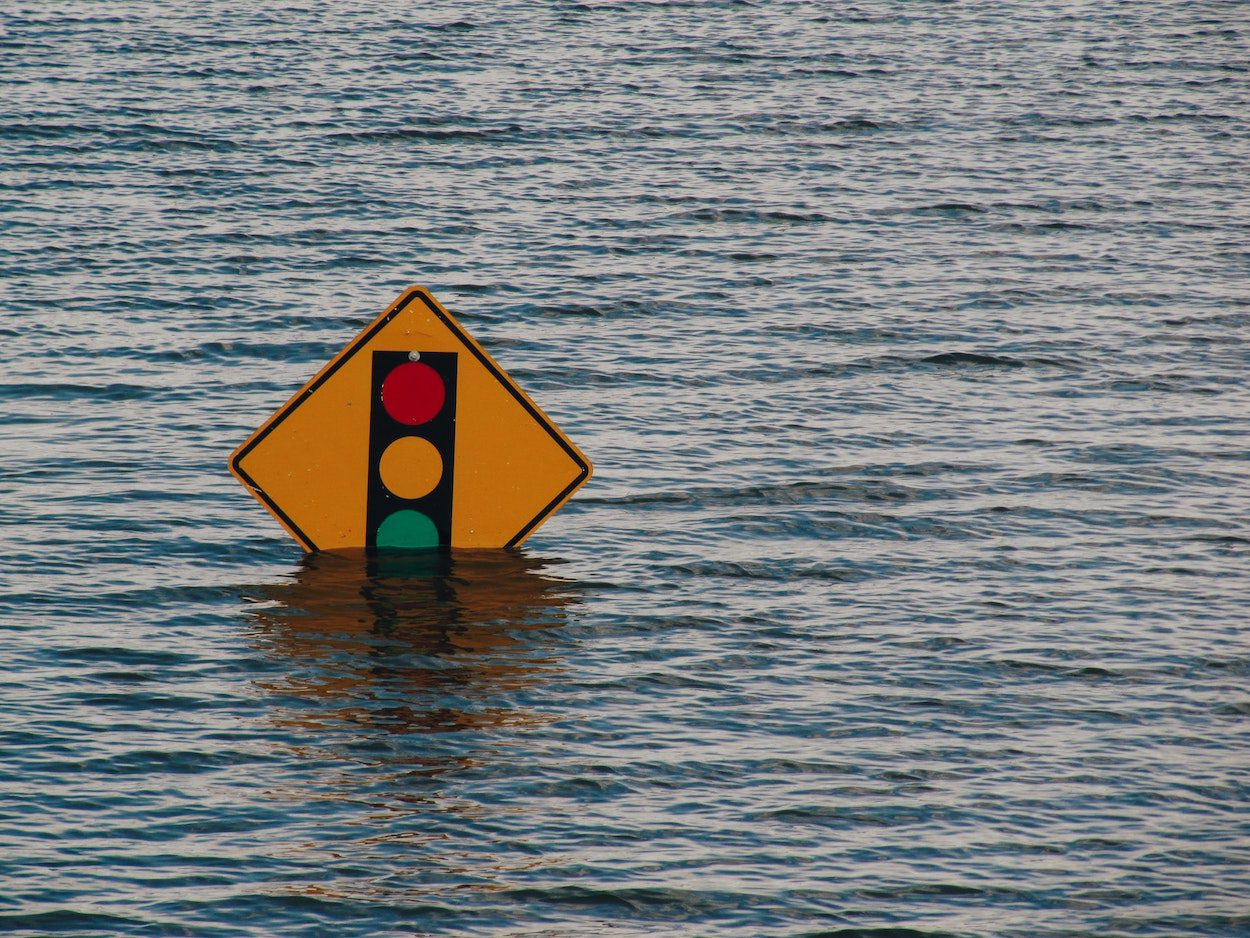 A traffic sign nearly covered by flood waters.